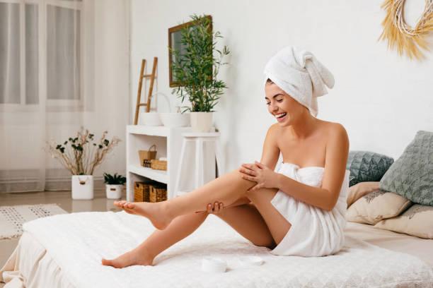 frau, die creme auf ihre beine aufwendet - körperpflege stock-fotos und bilder