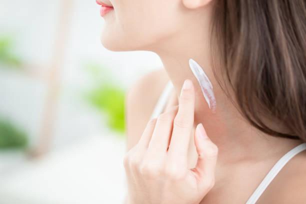vrouw toe te passen crème op de hals - nek stockfoto's en -beelden