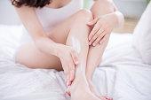 女性の足の上にクリームを適用します。