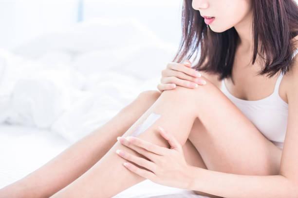 女性の足の上にクリームを適用します。 - 脛 ストックフォトと画像