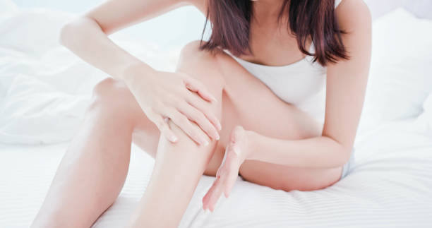 足にクリームを適用する女性 - 脛 ストックフォトと画像