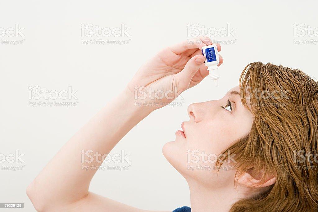 A woman applying eye drops stock photo