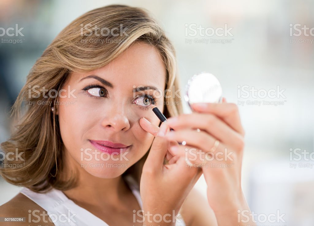 Woman applying eyeliner - makeup concepts stock photo