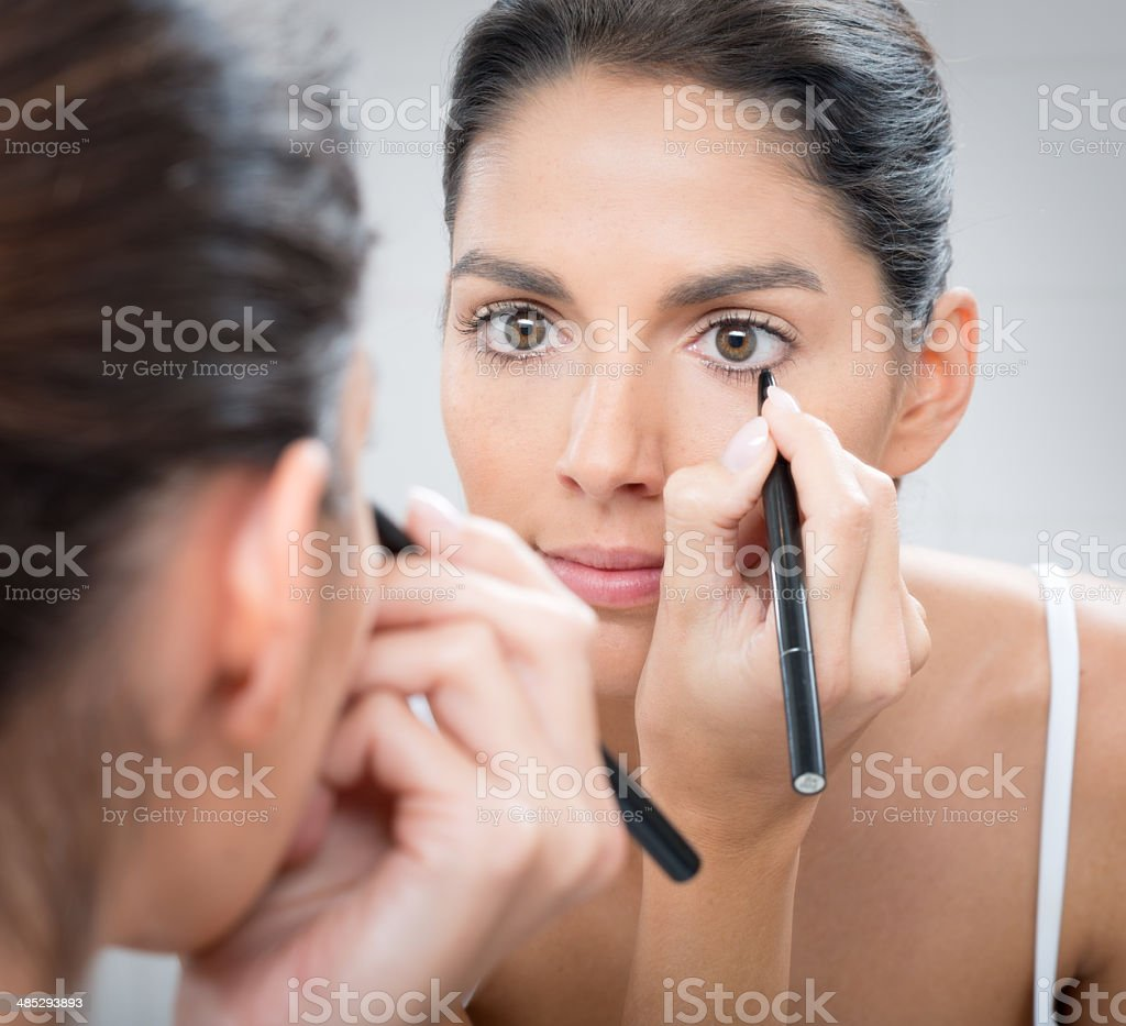 Woman applying Eyeliner Make-Up stock photo