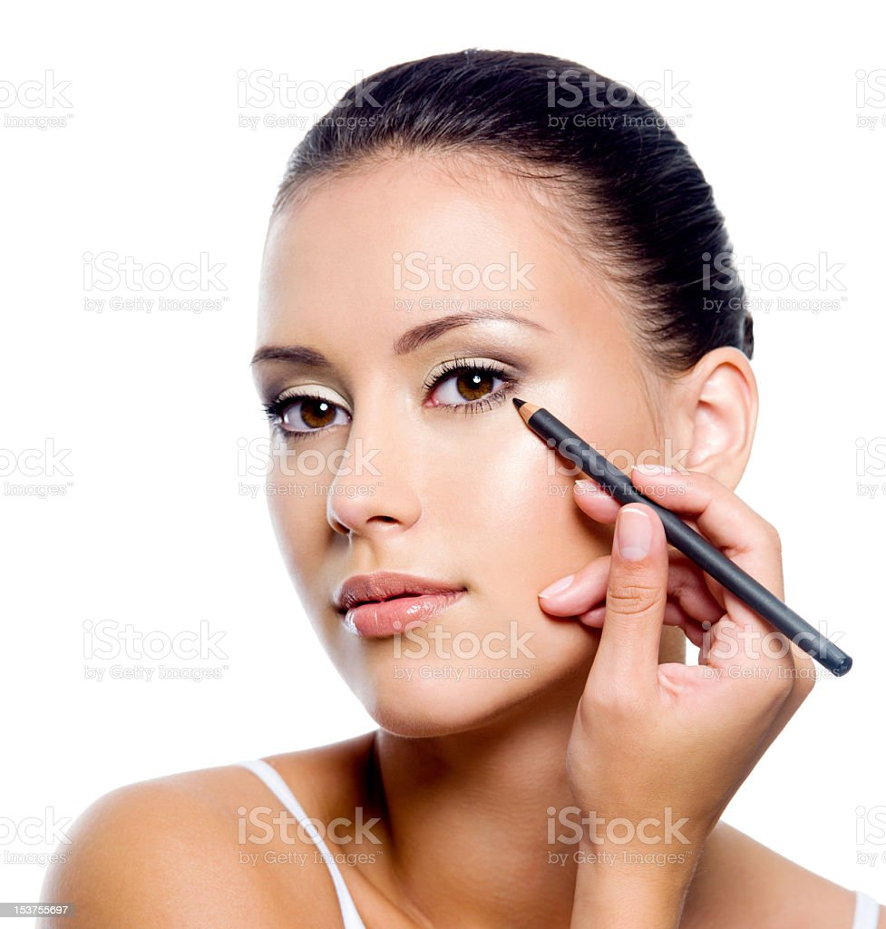 A woman applying eyeliner on her eyelid with a eyeliner stock photo