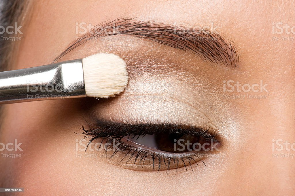 woman applying eyeshadow on eyelid stock photo