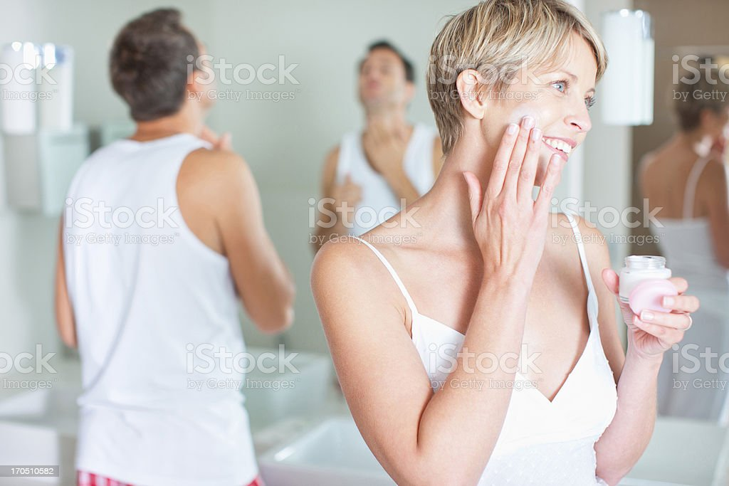 Woman applying face cream in the morning stock photo