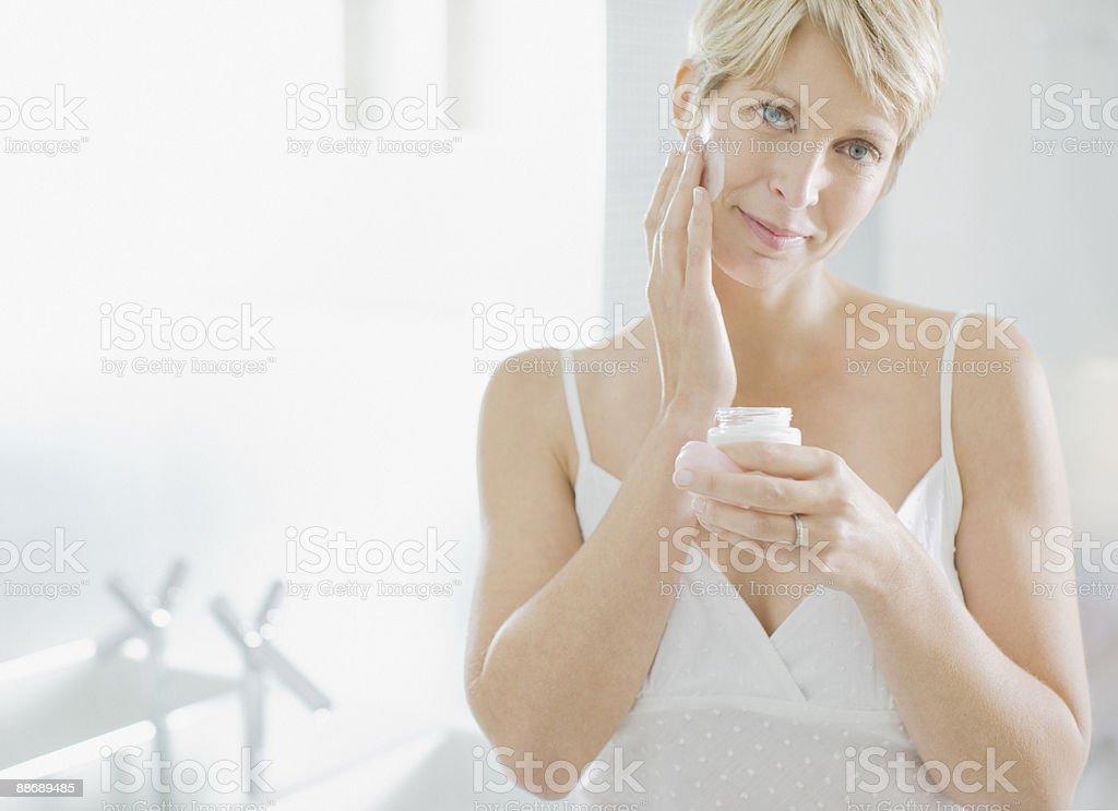 Femme appliquer la crème pour le visage dans le matin photo libre de droits