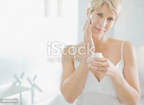 istock Woman applying face cream in the morning 88689485