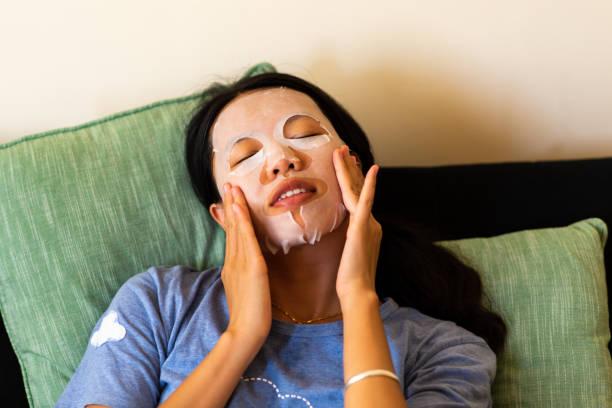woman applying face mask at home - sheet imagens e fotografias de stock