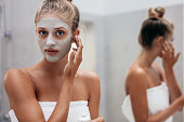 Close up shot of beautiful young woman doing beauty treatment on her face skin. Female applying facial mask in bathroom.