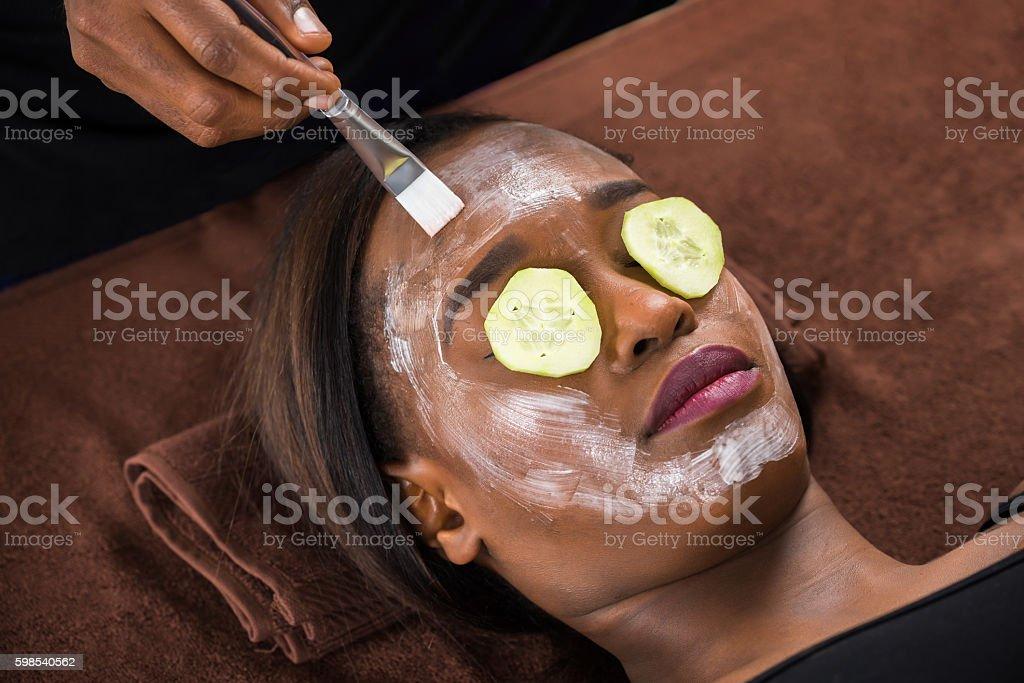 Woman Applying Facial Mask In Spa photo libre de droits