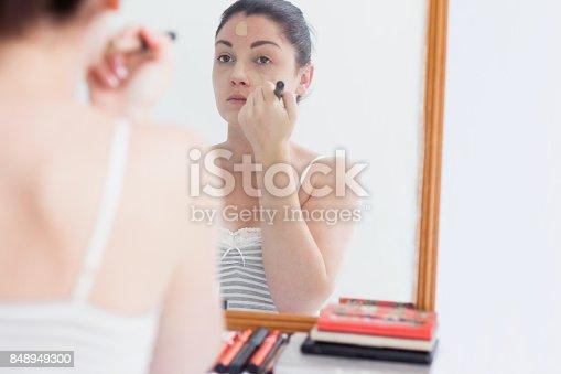 istock Woman applying foundation on face 848949300