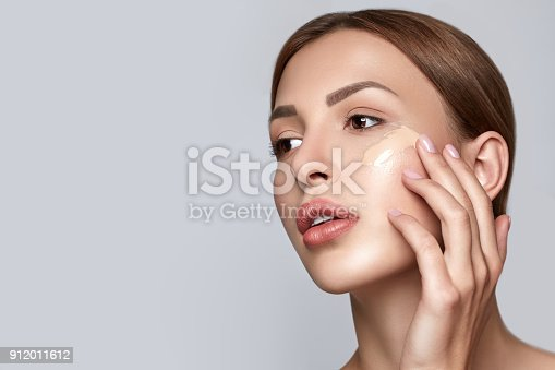 istock Woman applying foundation. Skin tone cream lines on woman face. Beautiful woman portrait beauty skin healthy and perfect makeup. Space for text. 912011612