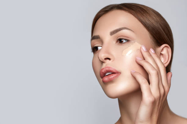 woman applying foundation. skin tone cream lines on woman face. beautiful woman portrait beauty skin healthy and perfect makeup. space for text. - make up imagens e fotografias de stock
