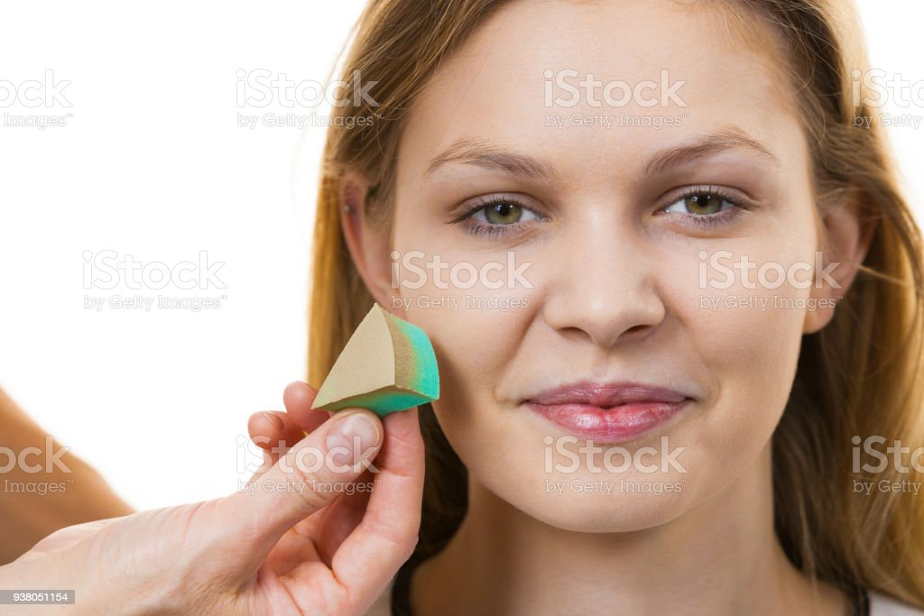 Woman applying foundation with sponge stock photo