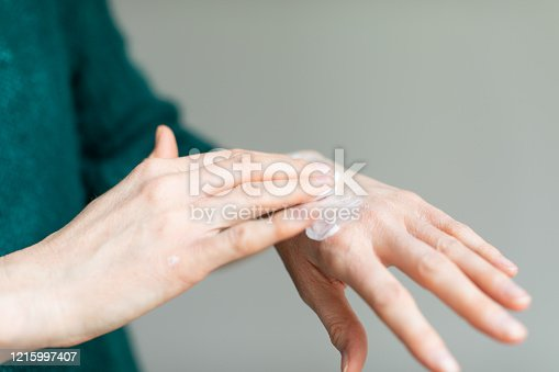 Washing hands frequently and hand sanitizer protect against COVID-19 but cause drying up of the skin. In the picture a woman applying skin moisturizer to relieve the pain of dry skin
