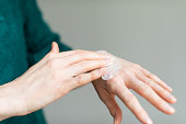 istock Woman applying hand cream to relieve the dry skin caused by hand sanitizer 1215997407