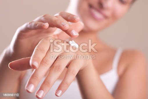 istock A woman applying hand lotion onto her hands 180956110