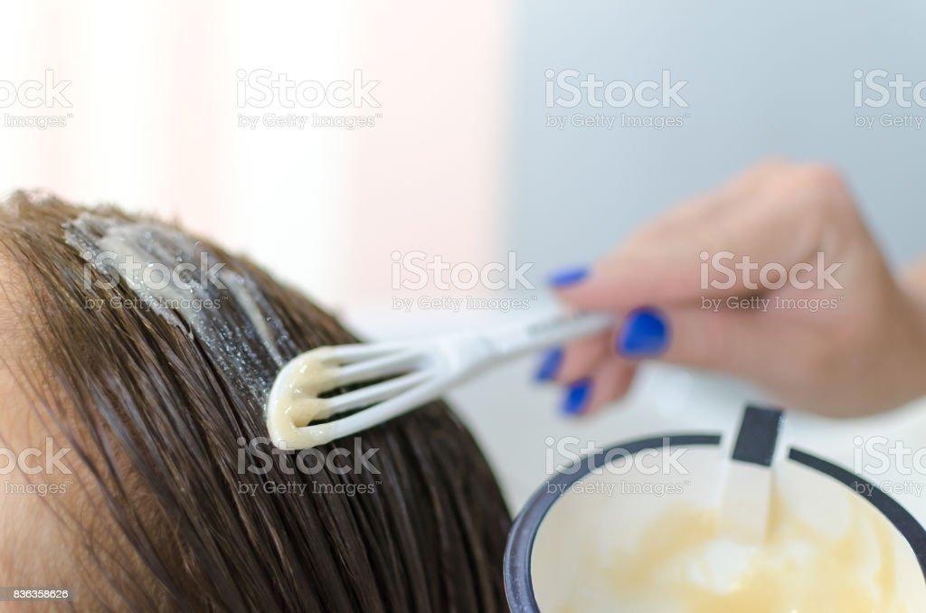 Aplicando máscara saudável no cabelo de mulher - foto de acervo