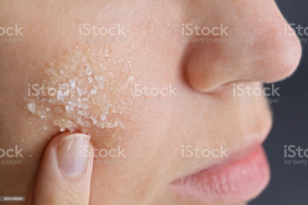 Woman applying homemade facial scrub from honey and sea salt stock photo