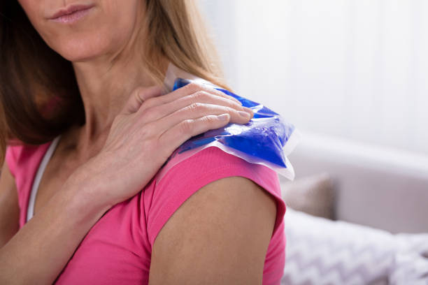 woman applying ice bag on her shoulder - crioterapia foto e immagini stock