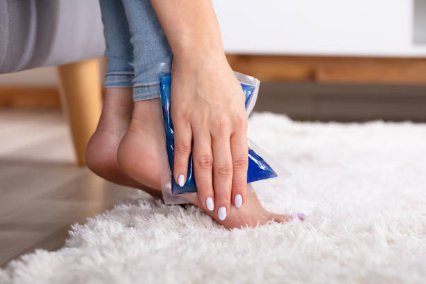 woman applying ice gel pack on her ankle - crioterapia foto e immagini stock
