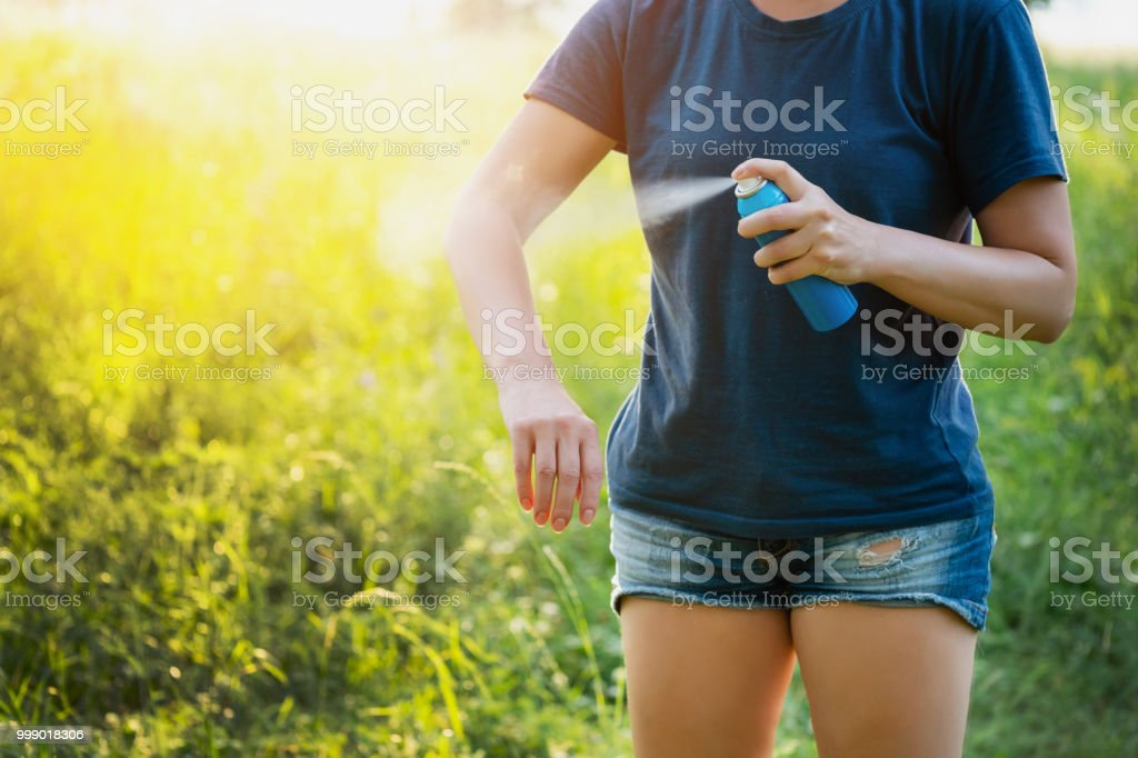 Woman applying insect repellent before forest hike beautiful summer day. stock photo