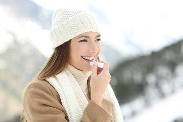 Mujer aplicar bálsamo para los labios en invierno cubierto de nieve - foto de stock