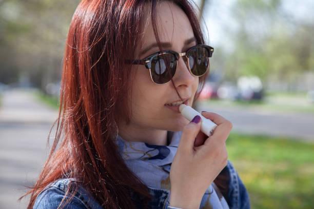 Woman applying lip balm stock photo