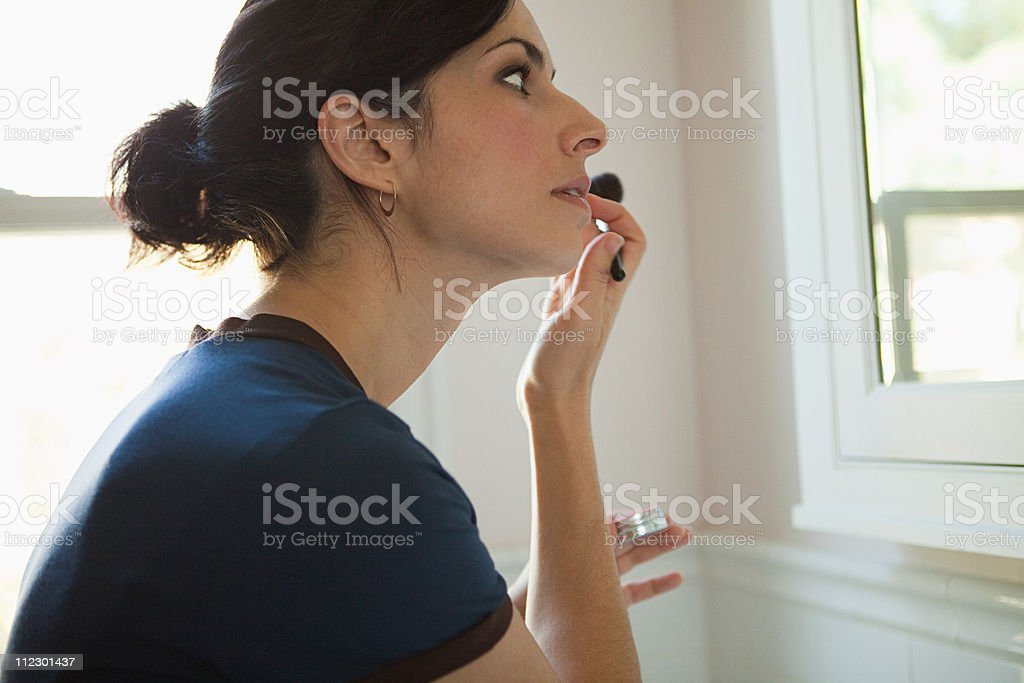 Woman applying lipgloss stock photo