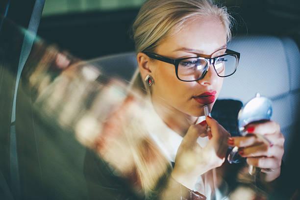 woman applying lipstick in a car - anzieh nacht stock-fotos und bilder