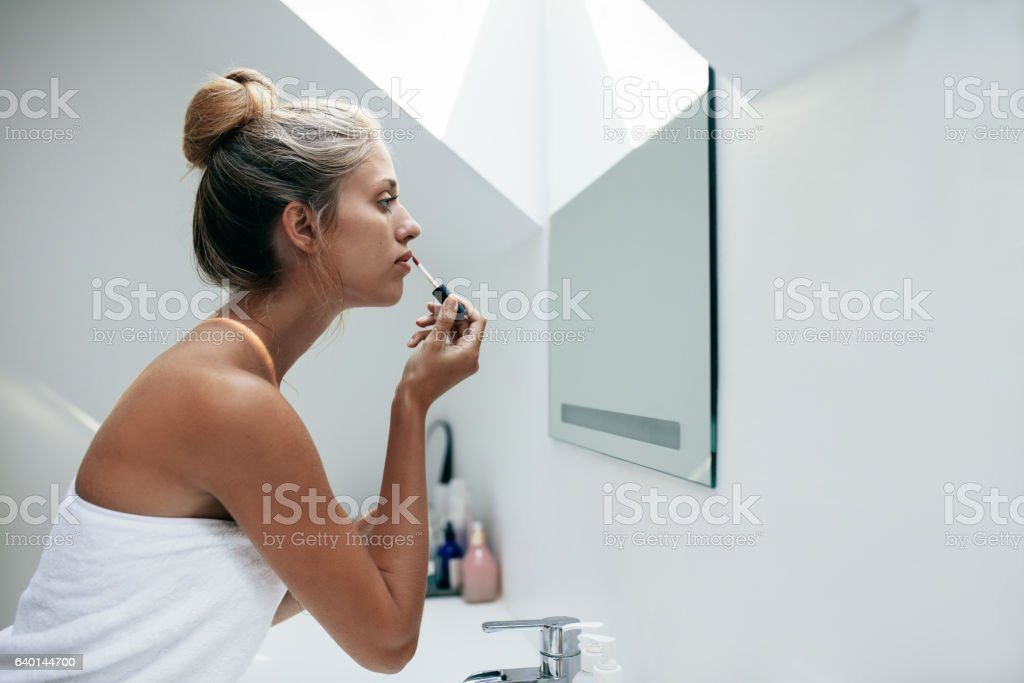 Woman applying lipstick in bathroom stock photo