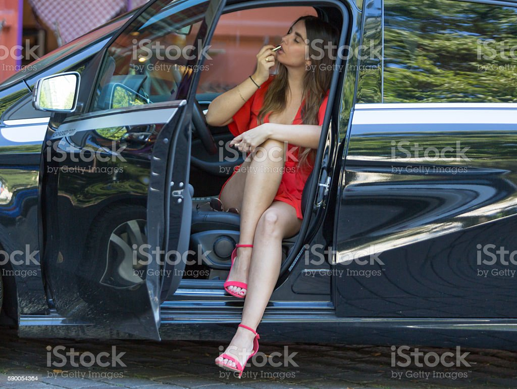 Woman applying lipstick in her car - foto de acervo