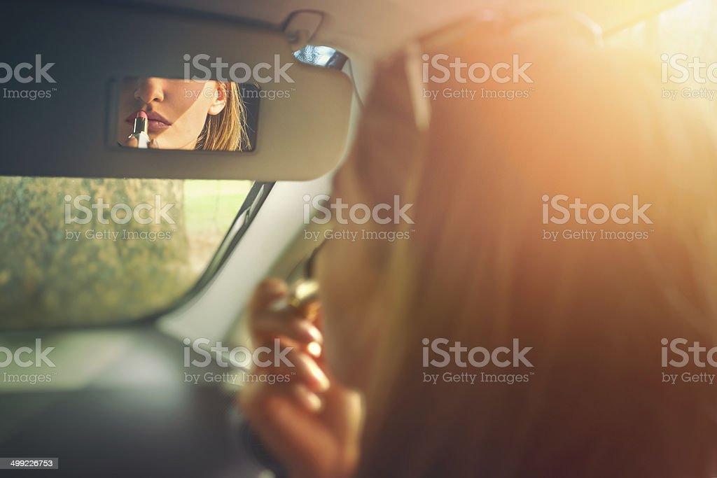 Mulher aplicando batom A car - foto de acervo