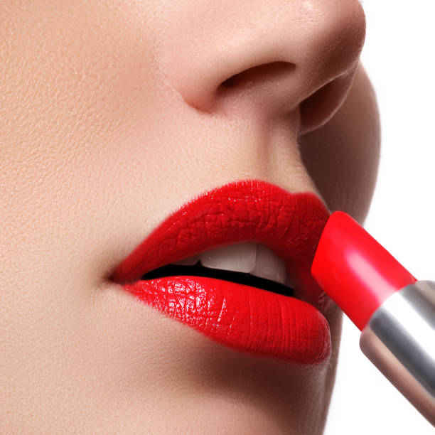 Woman applying lipstick. Model painted red lips stock photo