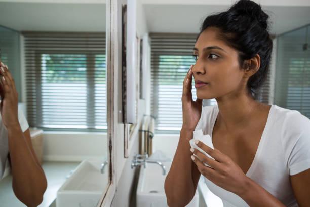 femme appliquant une lotion - cosmetique store photos et images de collection