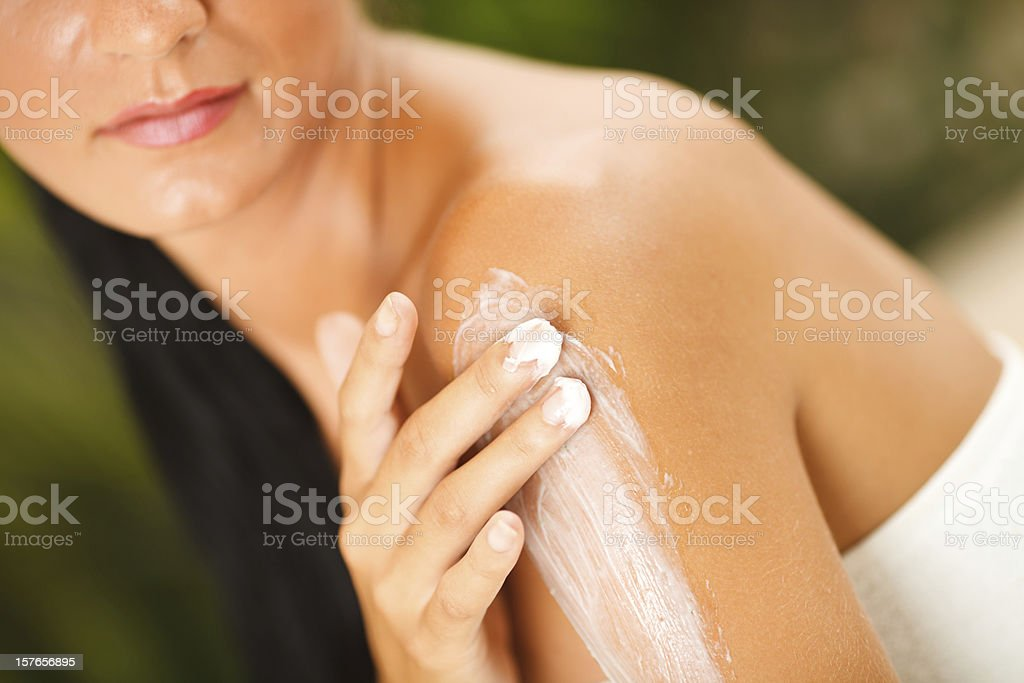 Woman applying lotion to shoulder stock photo