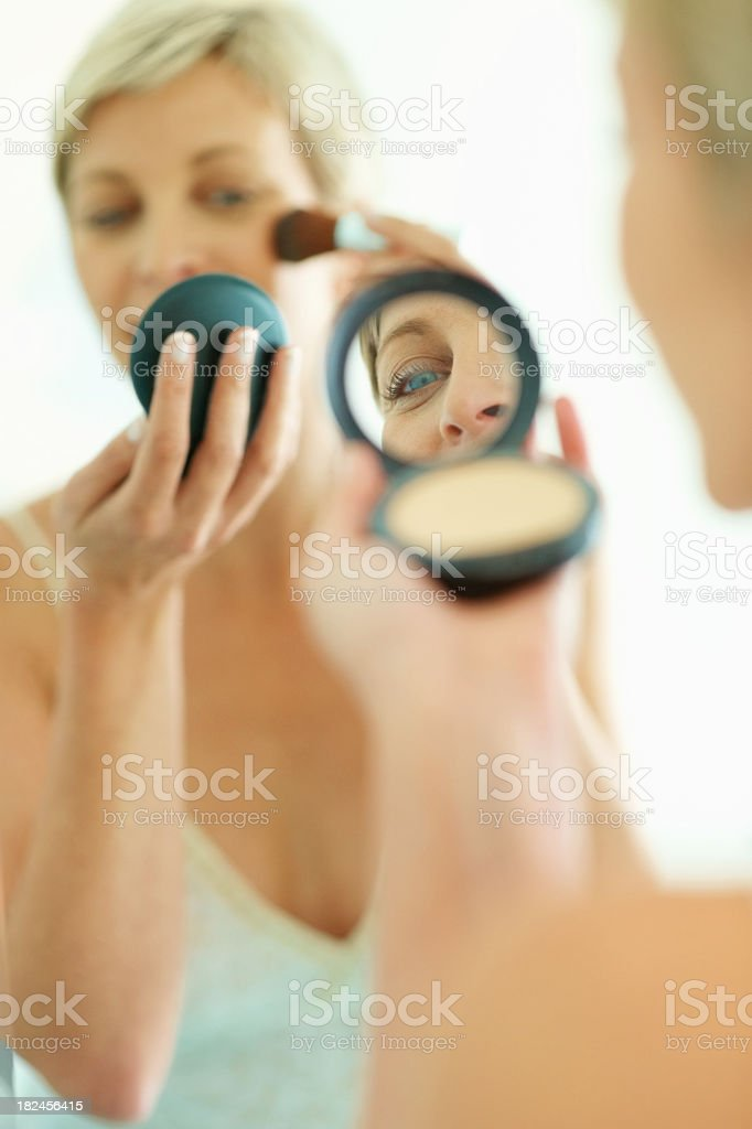Woman applying makeup looking in a mirror royalty-free stock photo