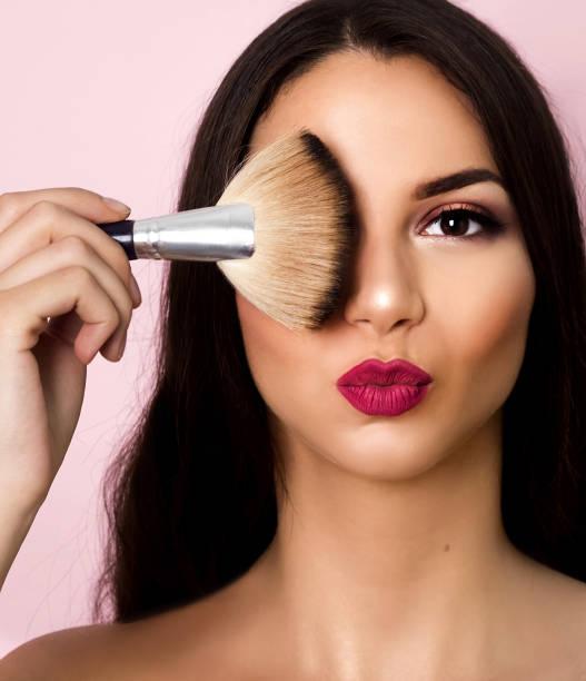 Mujer que aplica maquillaje - foto de stock