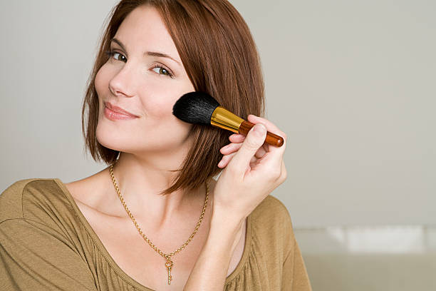 Woman applying makeup  blusher make up stock pictures, royalty-free photos & images