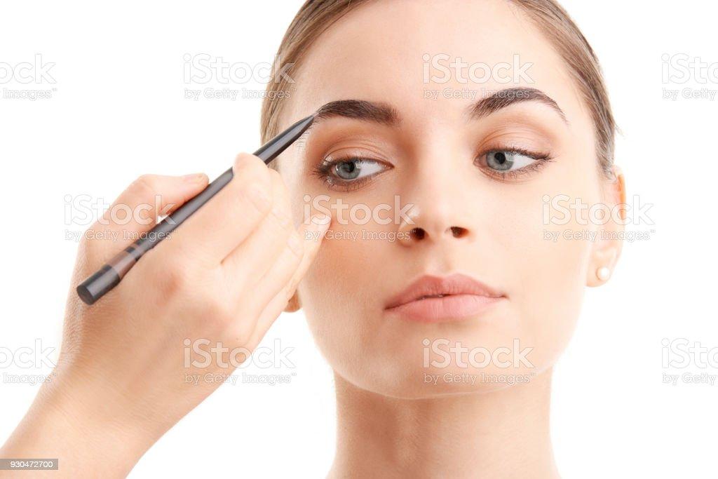 Woman applying makeup стоковое фото