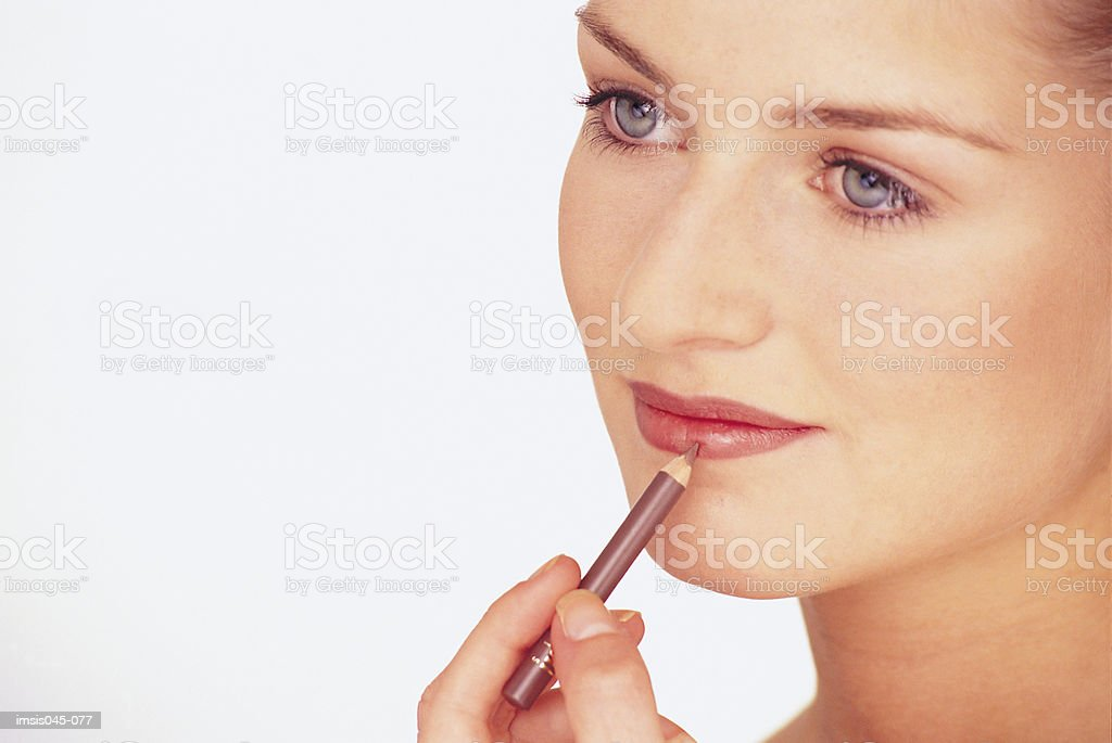 Woman applying make-up royalty free stockfoto