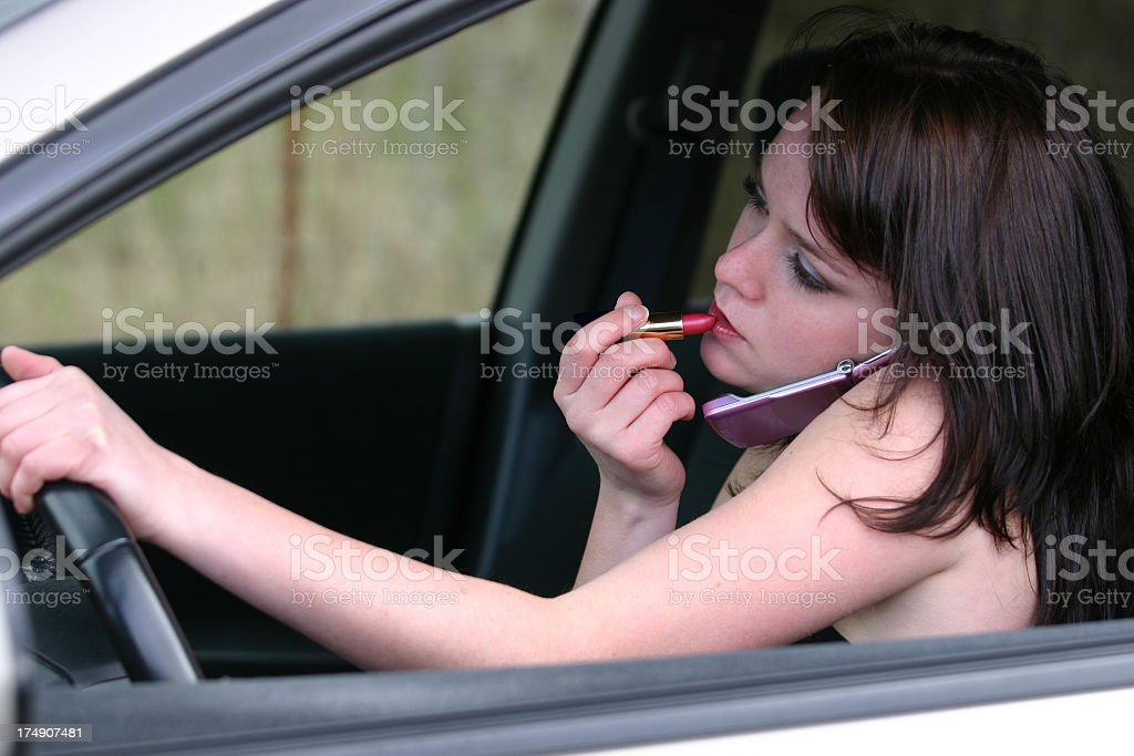 Woman applying makeup, talking on phone and driving stock photo