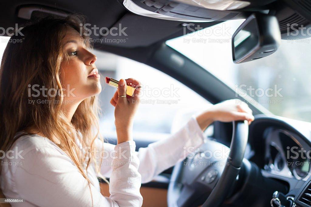 Mulher aplicando maquiagem enquanto dirigindo - foto de acervo
