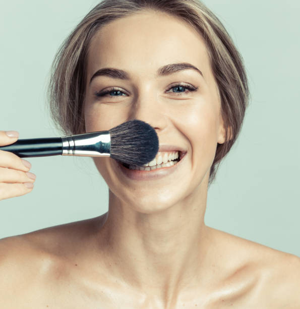 Woman applying make-up with a brush stock photo
