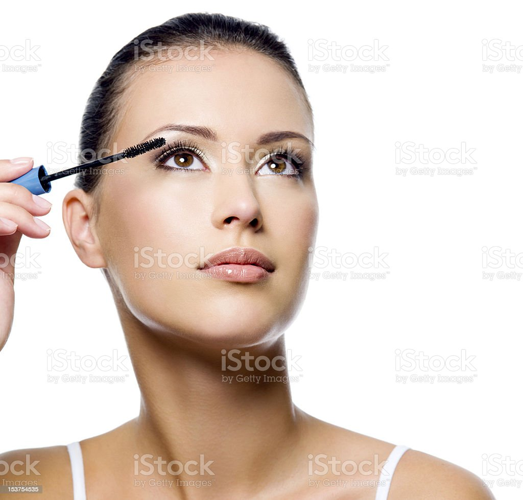 Woman applying mascara on eyelashes royalty-free stock photo
