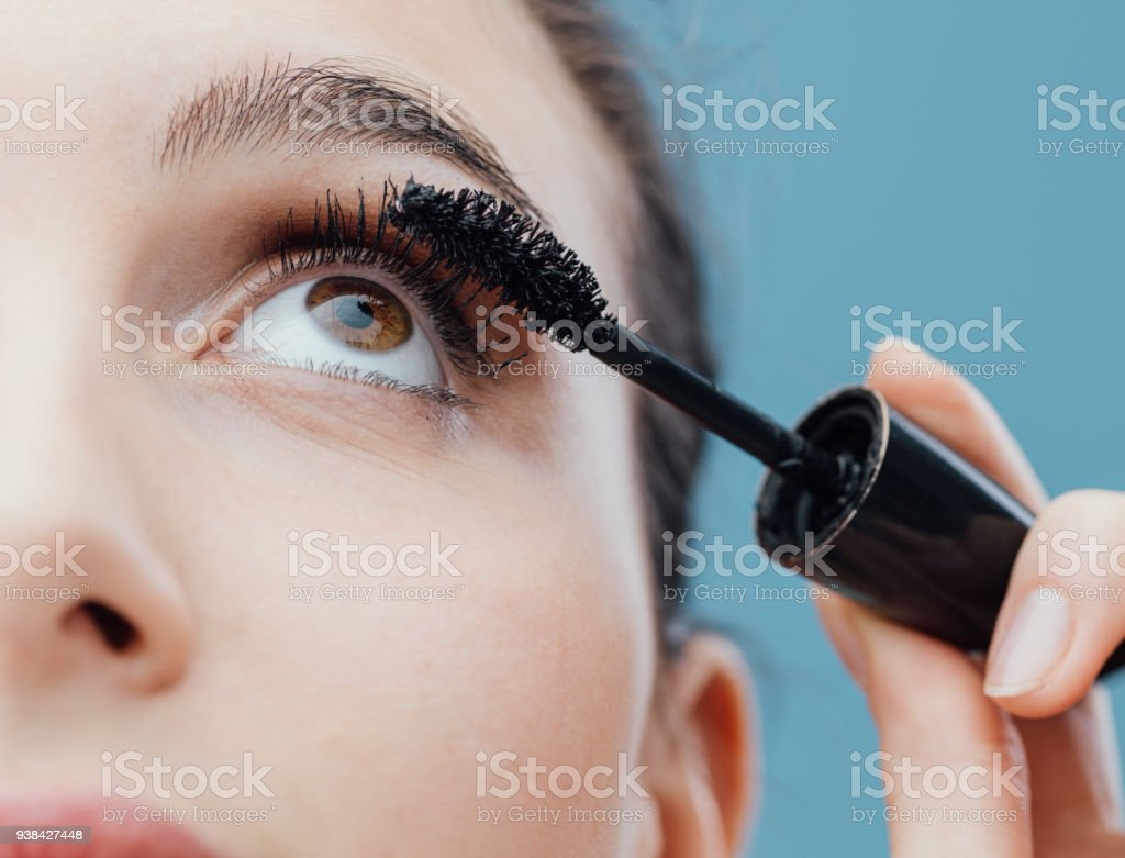 Woman applying mascara on her lashes stock photo