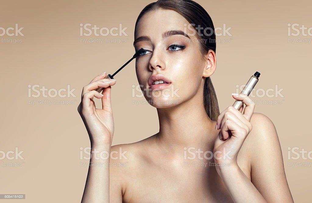Woman applying mascara on her long eyelashes stock photo