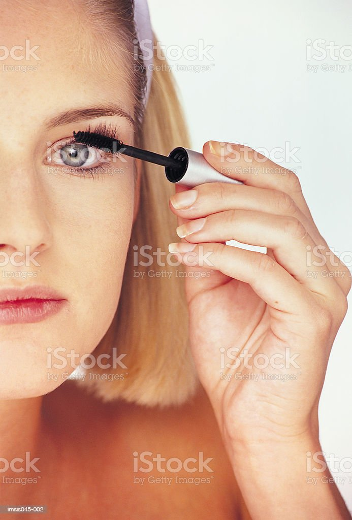 Woman applying mascara royalty free stockfoto